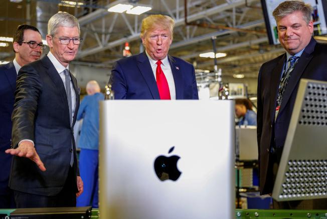 美國總統川普(中)參訪蘋果桌電組裝廠,蘋果執行長庫克(左)陪同參觀。路透