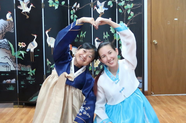 許多華人也參加2019第四屆奧蘭多韓國節活動,圖為中華學校董事長、中美協會前會長吳淑慧(左)與女兒試穿韓國服。(劉程驥提供)