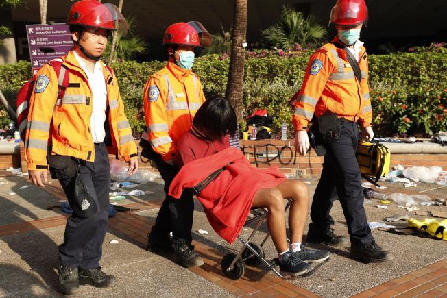 一名疑似受傷的示威者在醫護人員陪同下坐著輪椅離開理大。(歐新社)