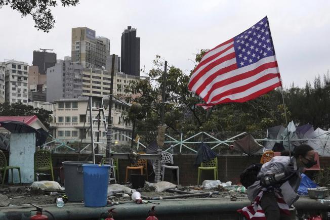 繼續留守在香港理工大學校園內的反送中示威學生20日撐起美國國旗。美國參院全票通過「香港民主人權法案」,引發北京強烈抗議。(美聯社)