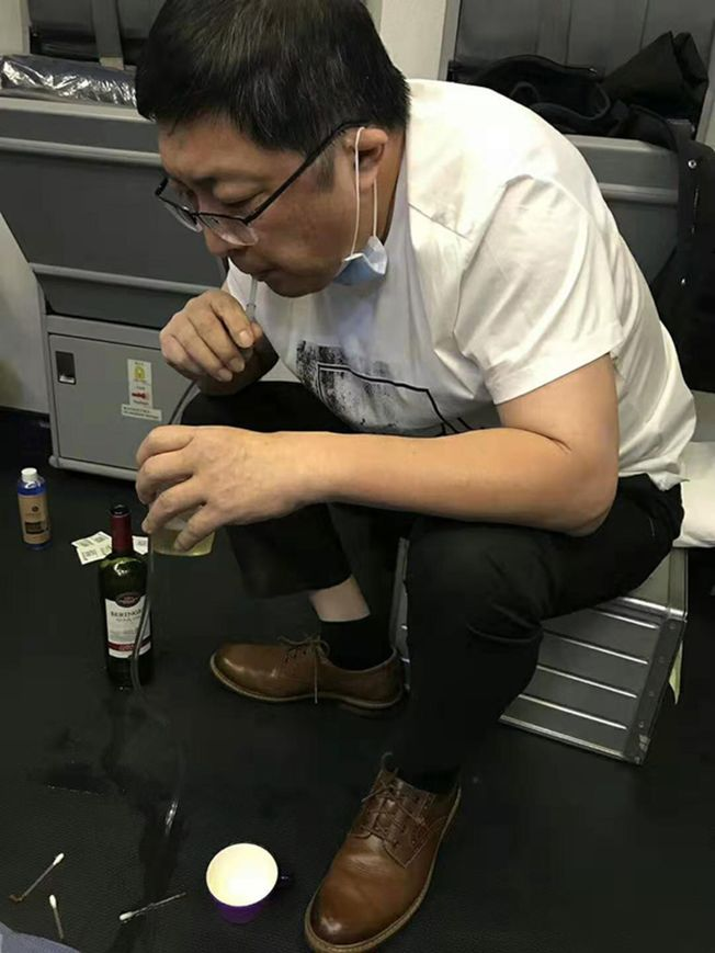 廣州飛往紐約的南航CZ399航班上,醫師張紅用導管吸出老人膀胱中的尿液。(取材自澎湃新聞/南航提供)