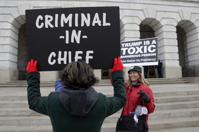 駐歐盟大使桑德蘭20日在國會作證彈劾川普,場外示威者高舉牌子稱川普是「犯罪主帥 」。(Getty Images)