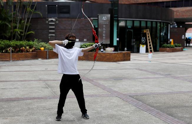 一名示威者在理大校區內練習射箭。理大被港警重重包圍已有5日,21日仍有至少50名死硬示威者不願撤出。路透