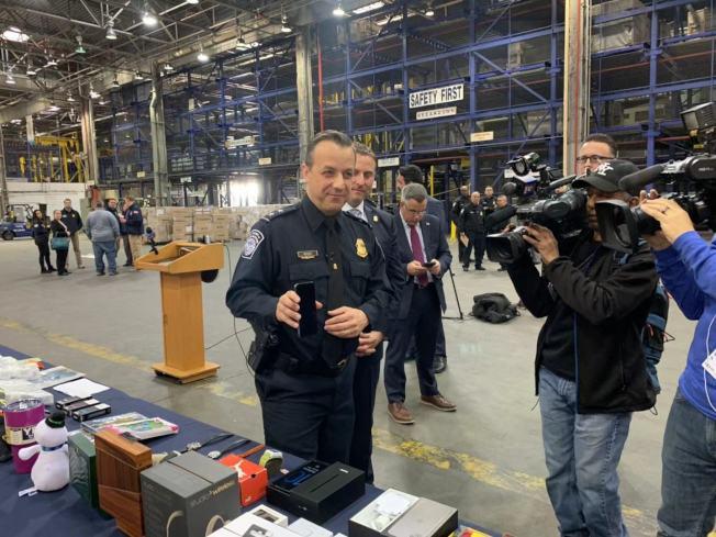 盧梭展示CBP上周截獲的一台仿冒iPhone11手機。(記者牟蘭/攝影)