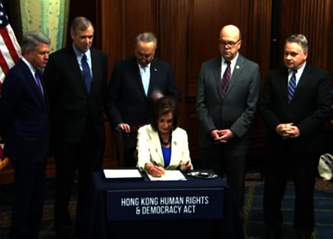 眾院議長波洛西(中坐)21日在眾院簽署「香港人權民主法案」,將送往川普總統簽字生效。參院少數黨領袖舒默(後中)及共和黨眾議員史密斯(右一)等兩黨眾議員在場觀禮。(取自視頻)