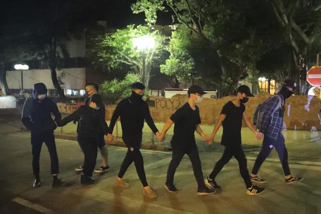 參與示威的香港理大學生21日向港警自首, 牽手就捕。(美聯社)