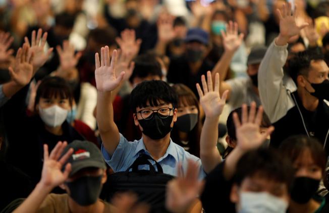 香港元朗Yoho購物中心示威者舉起手抗議。(路透)