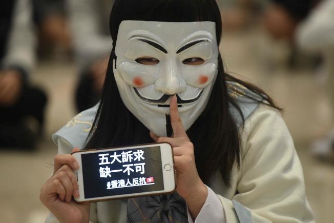 香港反送中抗議示威遠未結束,12月5日民陣將繼續上街。圖為21日戴面具示威者手機上標語是「五大訴求,缺一不可」。(Getty Images)