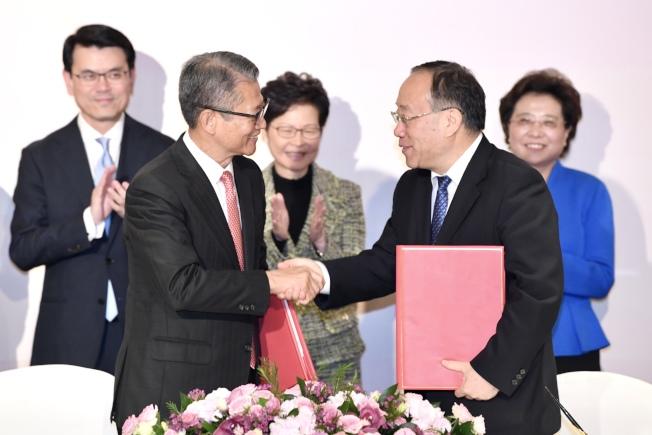 在特首林鄭月娥(後排中)見證下,香港財政司長陳茂波(前排左)21日與商務部副部長王炳南(前排右)簽署服貿協議文件後握手。(中通社)