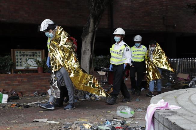 留守在理大的示威者21日披著保暖物品,由醫護人員陪同離開校園。(歐新社)