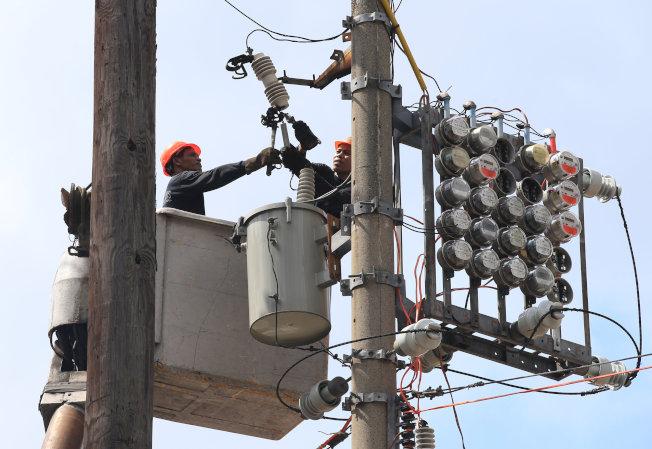 電力公司員工在馬尼拉大都會區的電線桿進行維修作業畫面。(路透)