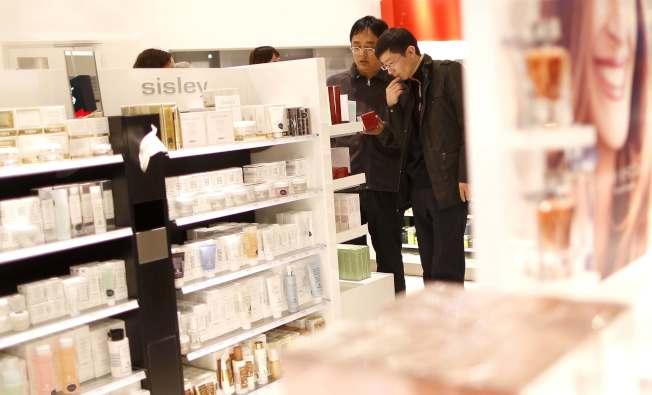 中國年輕男性開始愈來愈重視外表,投入化妝的行列。圖為男性在逛化妝品免稅店示意圖。(路透)