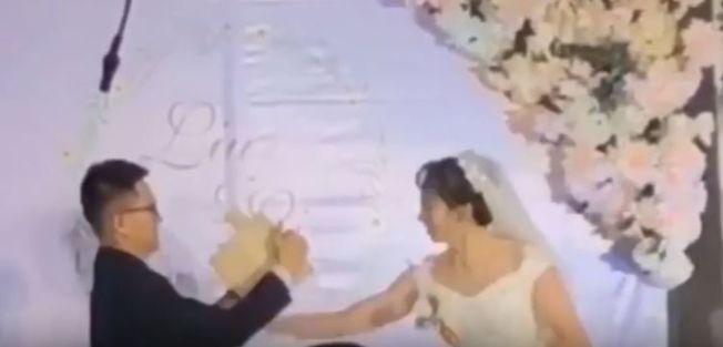 新娘劈斷新郎手裡的木板,驚呆賓客。(視頻截圖)