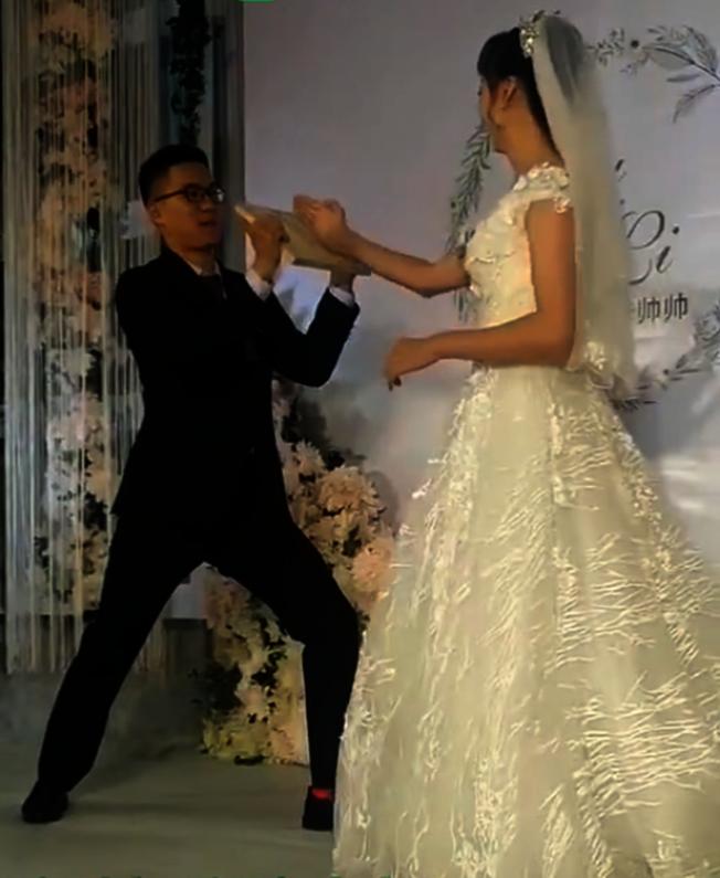 山東濰坊一對新人舉辦婚禮,新娘「才藝展示」劈新郎手裡的木板。(視頻截圖)