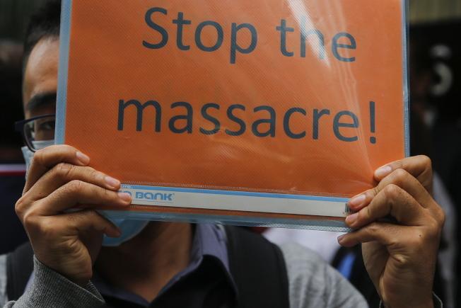 香港高等法院22日決定暫緩頒布禁蒙面法無效7天。圖為香港示威者舉牌要求「停止屠殺」。(歐新社)
