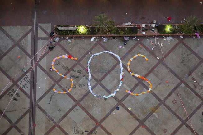 學者認為,「香港人權與民主法案」僅具象徵性,若川普否決法案,是愚蠢的行為。圖為香港理工大學示威者用衣服和頭盔排出「SOS」求救字樣。(美聯社)