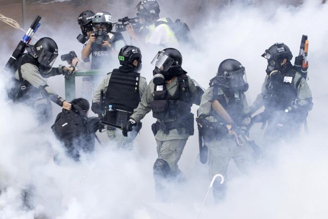 中美兩國在香港問題上較勁,還扯上貿易協議。圖為香港警察在催淚瓦斯煙霧中前進。(美聯社)