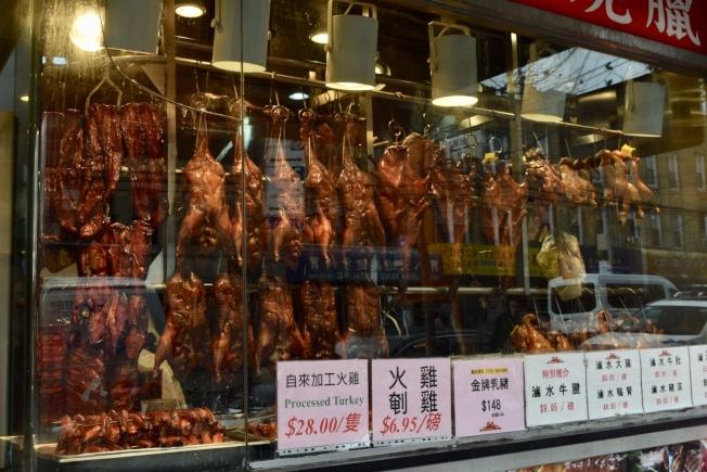 中餐館櫥窗掛滿各種燒烤,下方標明火雞價碼。(記者顏潔恩/攝影)