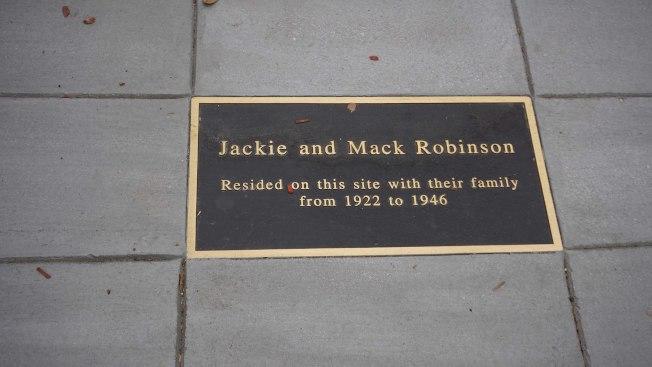 加州巴沙迪納(Pasadena)的平凡街區,人行道的水泥地上,鑲嵌著一塊黑底金邊的金屬告示,寫著「1922年到1946年間,傑基與馬克羅賓遜一家人住在這裡」。中央社