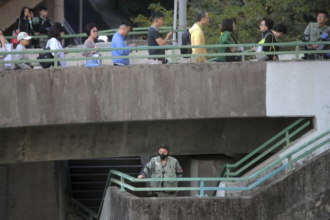 香港區議會周日選舉,選民投票踴躍,投票站外大排長龍,防暴警察也在旁戒備。(美聯社)