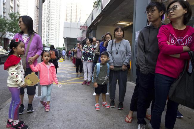 香港區議會周日選舉,選民投票踴躍,投票站外大排長龍。(美聯社)