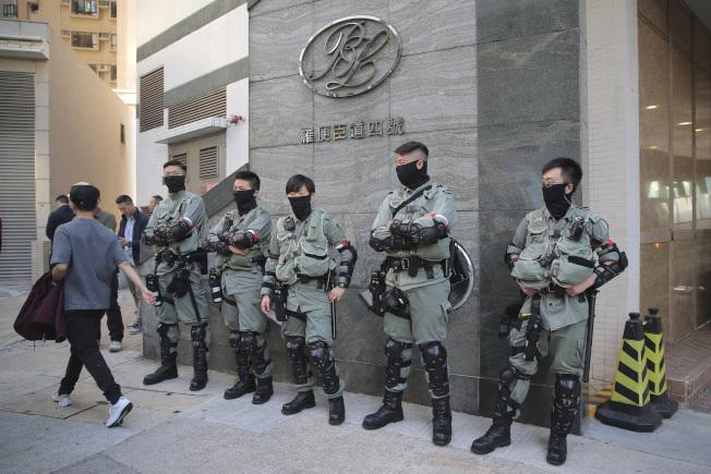 香港區議會周日選舉,防暴警察在投票站外戒備。(美聯社)