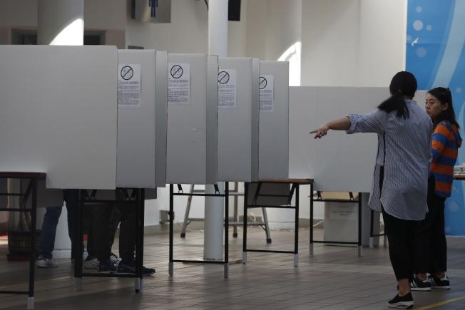 在半年反送中抗爭之後,香港區議員選舉備受各方矚目。圖為選務工作人員布置投票站。(歐新社)