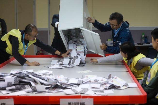 灣仔一家投票站工作人員將選票倒入點票檯上。(中央社)