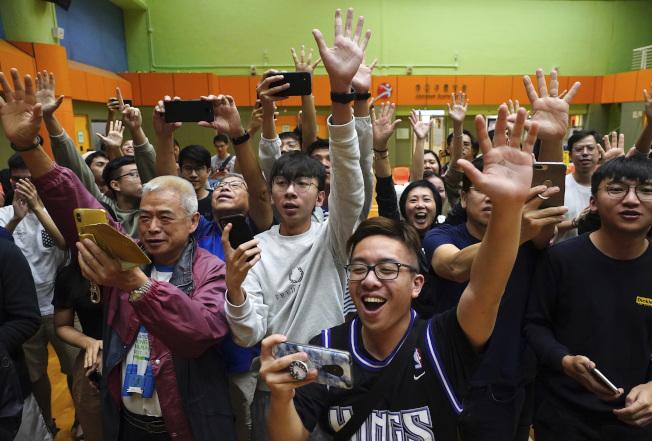 香港區議會選舉24日開票結果,泛民主派大勝,年輕支持者雀躍歡慶。(美聯社)