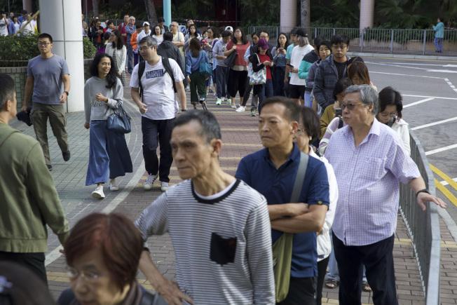 香港區議會選舉24日投票,投票率創香港歴史新高,許多人一早就去排隊投票。(美聯社)