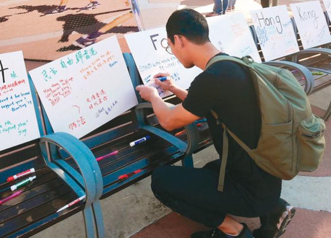 黃同學在簽名板上寫下支持的話語。(本報記者/攝影)