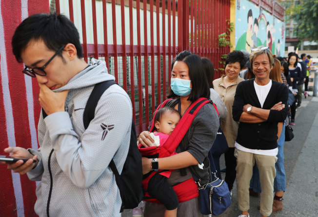 一大早就有人排隊投票,首投族都站出來,踴躍度創香港歷史新高。(路透)