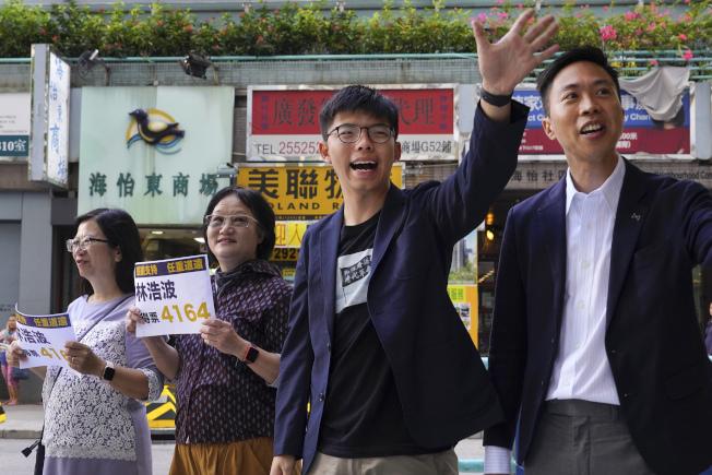 反送中的黃之鋒是唯一被北京點名取消候選資格的人,他24日恭喜民主派候選人Kevin Lam當選。(美聯社)