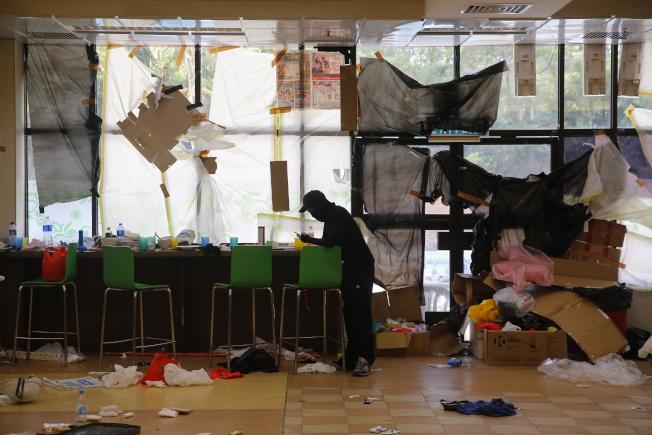 一名黑衣蒙面示威者站在理大校內的餐廳,餐廳內零亂不堪、雜物亂置。(歐新社)