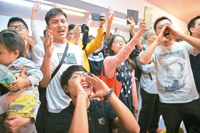 香港泛民主派支持者25日凌晨高聲歡呼,慶祝親北京的區議員何君堯落選。 (美聯社)