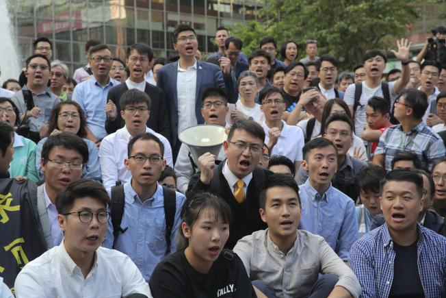 一群剛當選的區議員25日在香港理大前聚會,高喊警方釋放被圍困的理大學生。香港24日區議會選舉,支持反送中的泛民派大勝。(美聯社)