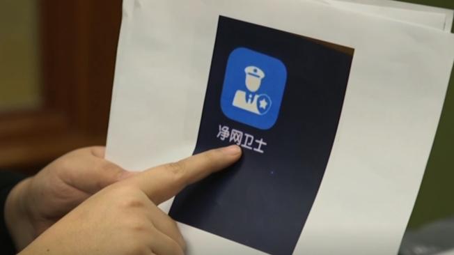 維吾爾族受害者Zumrat Dawut展示中國警方在他們手機中安裝用於監視的應用程式。(美聯社)