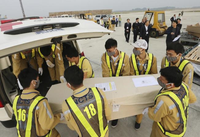 在越南內排國際機場,工作人員將棺材卸下。19具受害者遺體27日從英國運回越南。(美聯社)