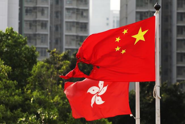 美國總統川普已簽署「香港人權與民主法案」。圖為在反送中抗議中被燒的五星旗(前)。路透