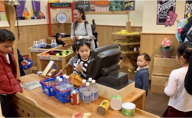 孩子們在超市刷卡購物。(記者尚穎/攝影)