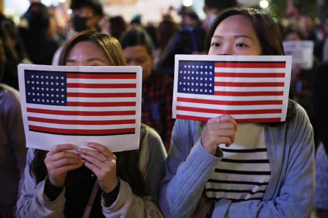 香港反送中示威者,不分老小28日集會,有人拿著美國國旗感謝美國總統川普簽署法案。(Getty Images)