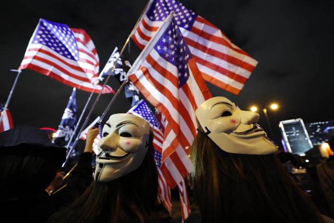 香港反送中示威者28日晚在中環愛丁堡廣場舉行「『香港人權與民主法案』感恩節集會」,感謝美國總統川普簽署法案。有人拿著美國國旗揮舞,高唱美國國歌。(Getty Images)