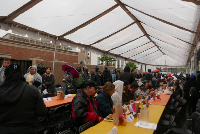 28日不少周圍社區的遊民或低收入民眾仍冒雨前來該中心享用一頓熱騰騰的火雞餐。(記者李雪/攝影)