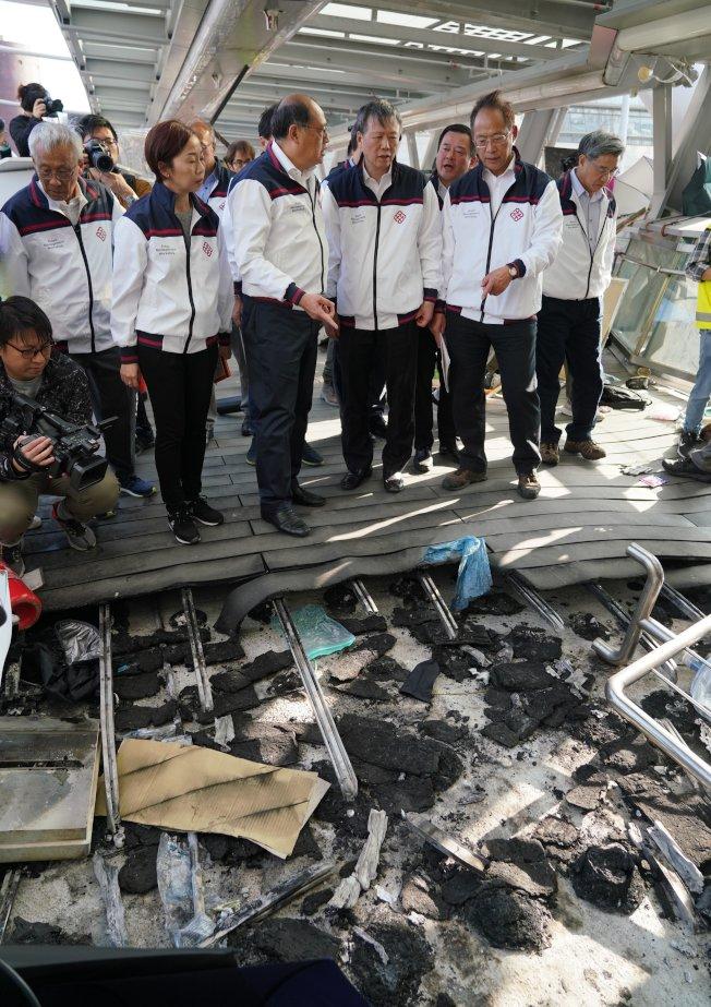 香港理工大學校方人員進入校園察看被破壞情況,校長滕錦光(右三)表情凝重的看著被毀壞的設施。(中通社)