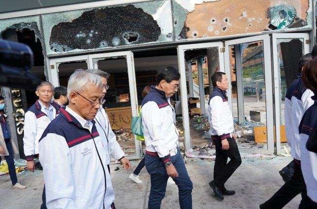 香港理工大學校方人員進入校園察看被破壞情況,經過被嚴重破壞的星巴克咖啡店。(中通社)