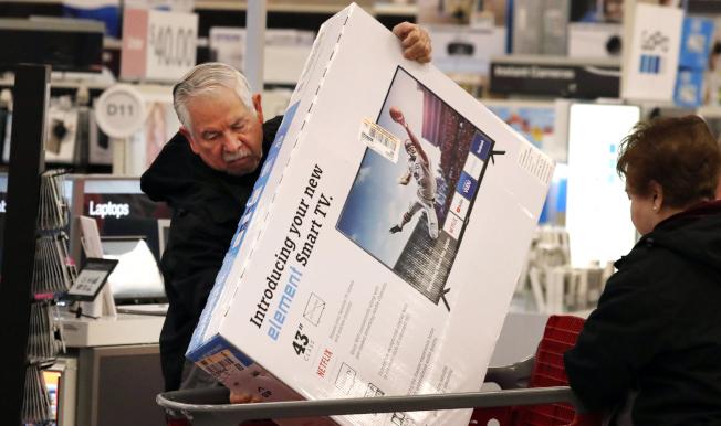 家電用品是消費者最熱愛的貨品。一名消費者自德州Frisco的目標商店搬回平板電視。(美聯社)