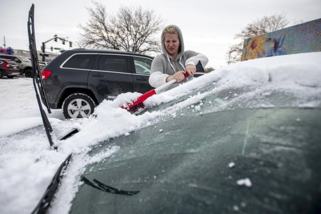 強風暴雪侵襲加州到中西部地帶,加上其他地區豪雨成災,打亂了感恩節過後趕著回家的數以百萬計旅客的行程。圖為柯羅拉多州居民30日上午外出前,刮除結在車窗上的冰。(美聯社)