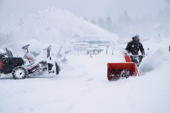 強風暴雪侵襲加州到中西部地帶,加上其他地區豪雨成災,打亂了感恩節過後趕著回家的數以百萬計旅客的行程。圖為加州大熊山度假中心工作人員清除步道上的積雪。(美聯社)