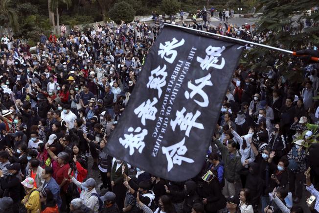 港人11月30日參與中環遮打花園「老幼攜手、和你同行」集會,反對港警過度使用催淚彈;集會期間,示威者揮舞「光復香港,時代革命」旗幟,高舉手掌表達「五大訴求,缺一不可」。(美聯社)