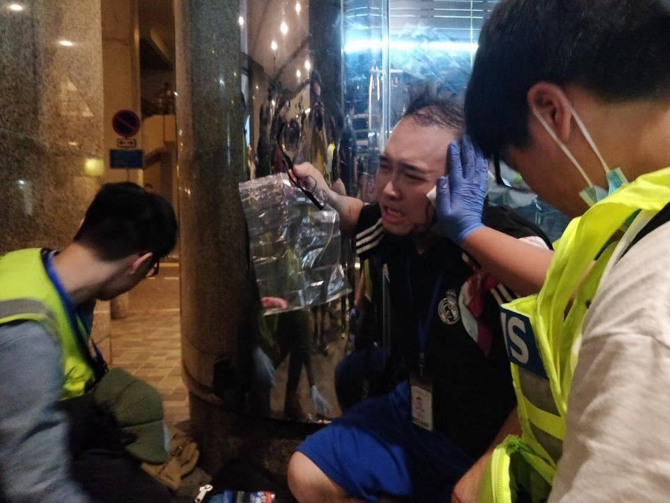 趙家賢蹲在地上接受治理,右手拿著眼鏡和一個透明膠袋,袋中有他自己的耳朵殘肉。(取材自林卓廷臉書)